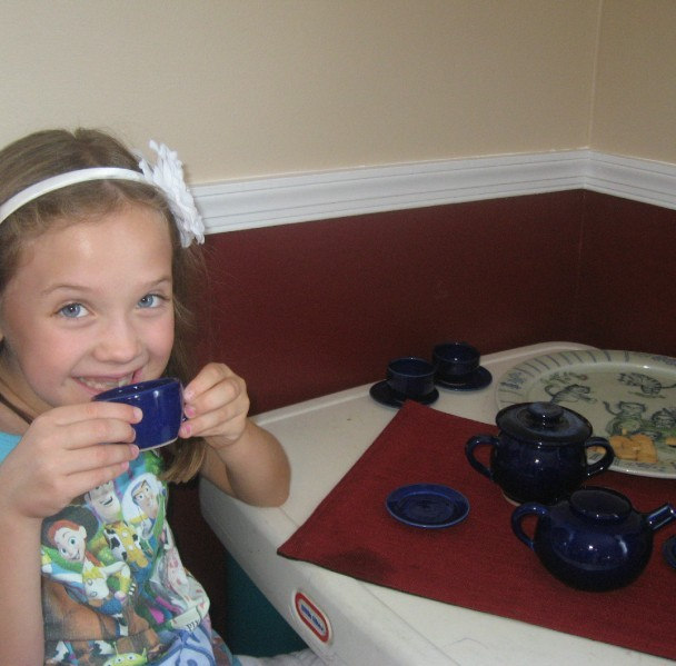 Katie sipping lemonade from uncle Dave's hand made tea set.